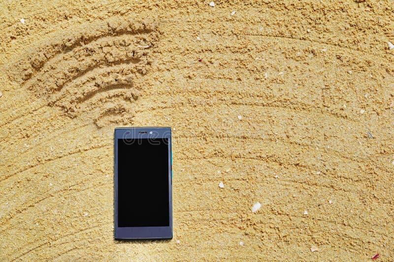 Teléfono móvil en la arena y la escritura de los símbolos de Wi-Fi fotografía de archivo