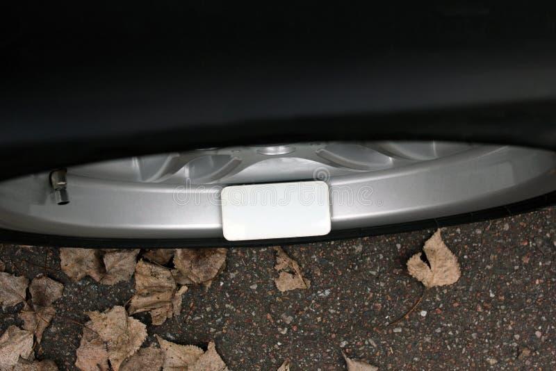 Teléfono móvil en la rueda de un coche imagen de archivo