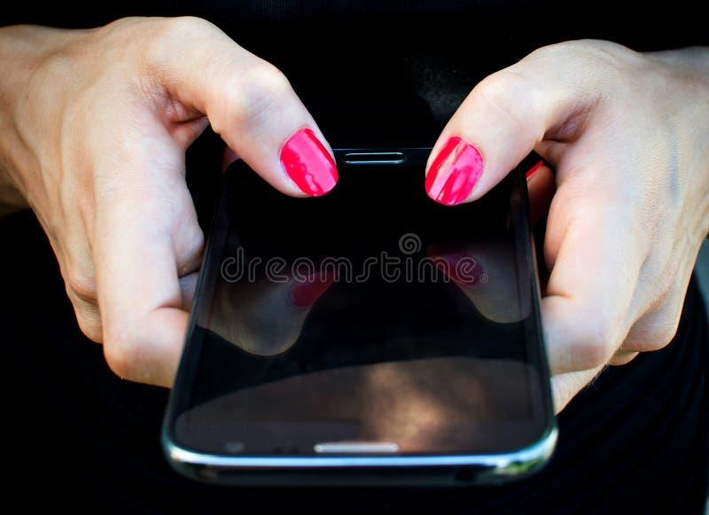 Teléfono móvil en mano de la mujer foto de archivo libre de regalías