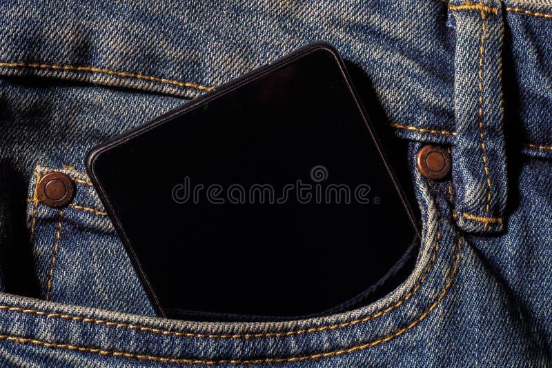 Teléfono móvil en sus tejanos con bolsillos Fotos del primer fotos de archivo