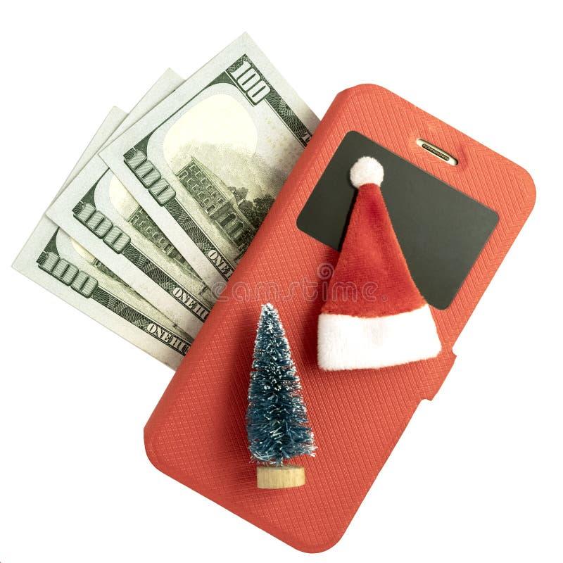 Teléfono móvil en una caja roja, un árbol de navidad del recuerdo y un sombrero de Santa Claus y trescientos dólares americanos e imagen de archivo