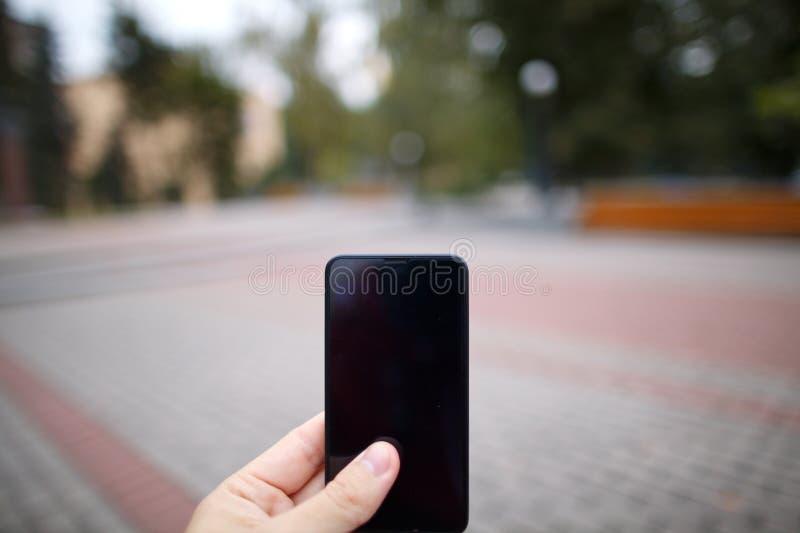 Teléfono móvil en una mano en el fondo borroso del bokeh Nuevas tecnologías, el renombre de usar smartphones en vida imagen de archivo libre de regalías