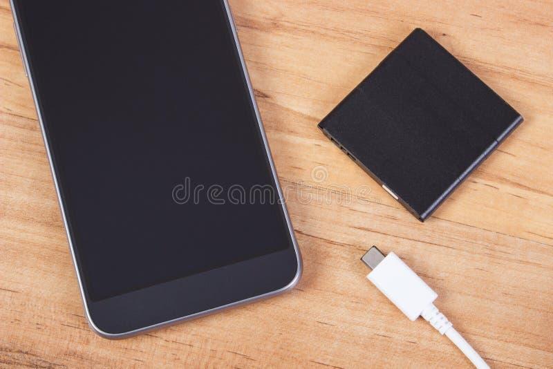 Teléfono móvil, enchufe del cargador y batería del teléfono imágenes de archivo libres de regalías