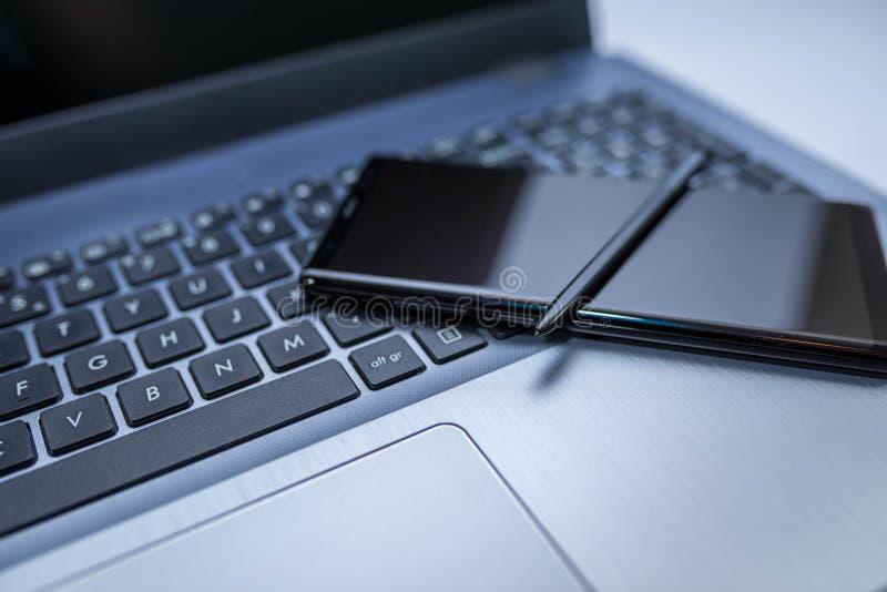 Teléfono móvil moderno con la aguja en el teclado de ordenador portátil, profundidad del campo baja imagenes de archivo
