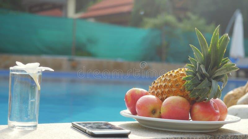 Teléfono móvil, placa con las frutas, vidrio de agua con la flor del frangipani por el cierre de la piscina fotos de archivo