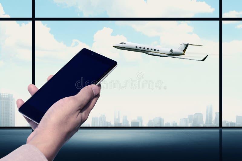 Teléfono móvil que celebra en el aeropuerto foto de archivo libre de regalías