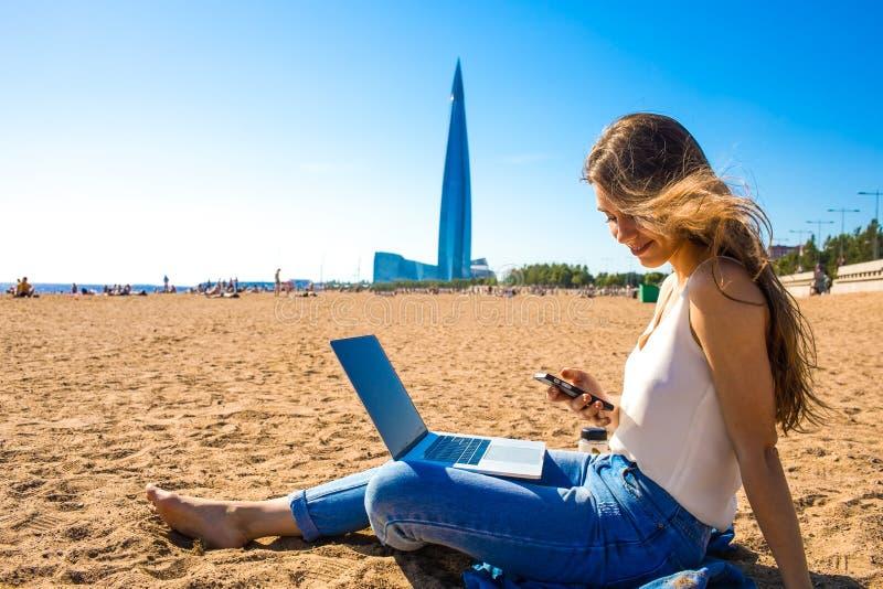 Teléfono móvil que usa femenino después del trabajo de la distancia sobre el dispositivo del cuaderno imagen de archivo libre de regalías