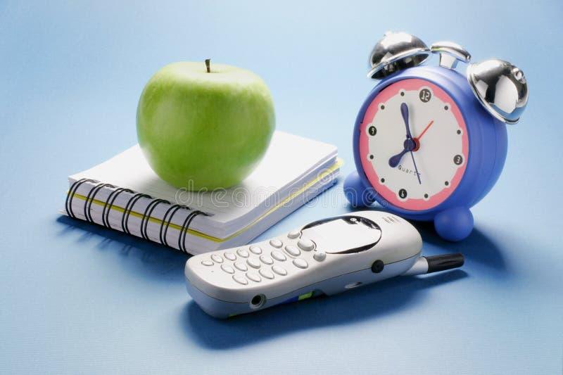 Teléfono móvil, reloj y Apple fotografía de archivo libre de regalías