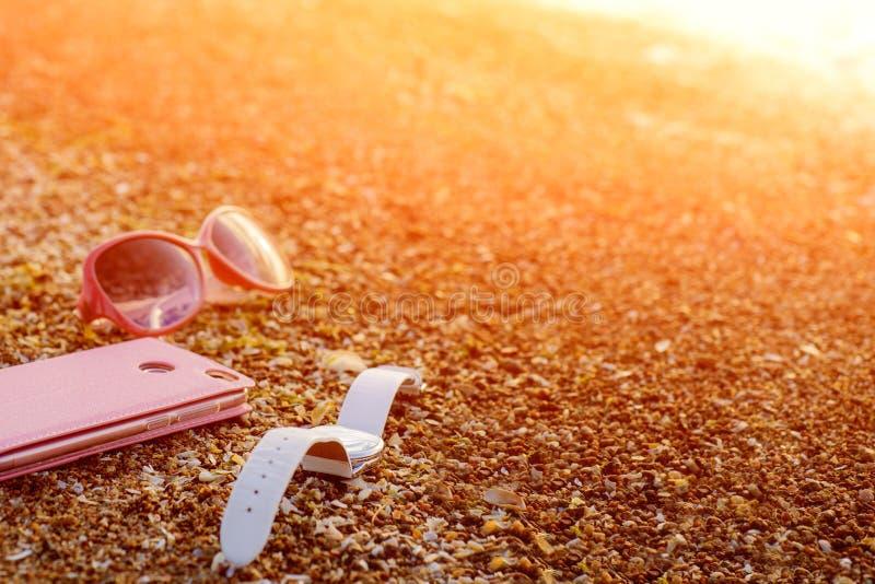 Teléfono móvil rosado, reloj blanco y vidrios rosados en Sandy Sea Beach With Waves y la luz del sol Teléfono elegante moderno fotografía de archivo