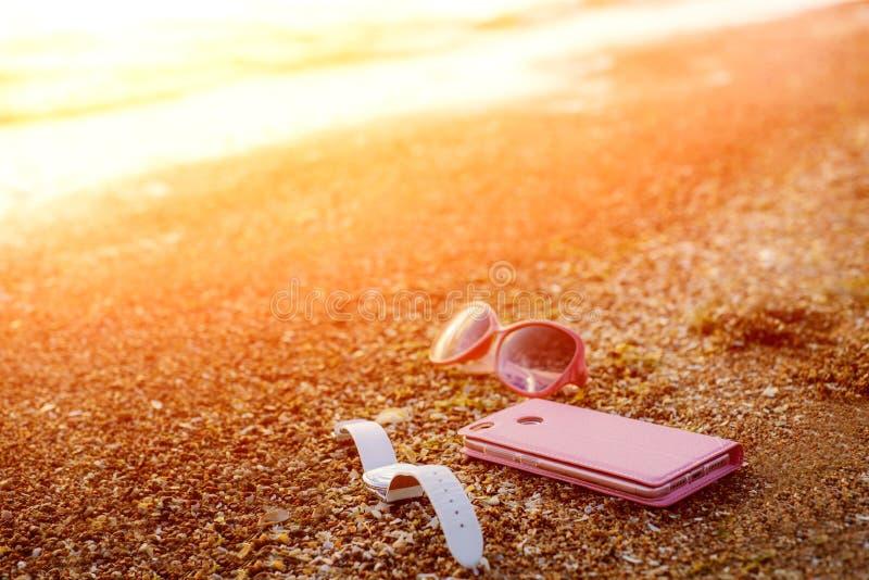 Teléfono móvil rosado, reloj blanco y vidrios rosados en Sandy Sea Beach With Waves y la luz del sol Teléfono elegante moderno fotos de archivo libres de regalías