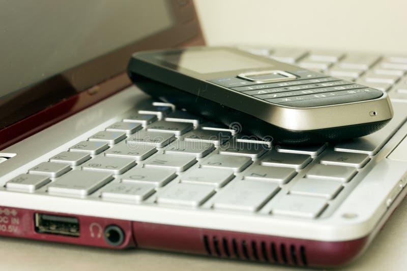 Teléfono móvil sobre el teclado de la computadora portátil imágenes de archivo libres de regalías