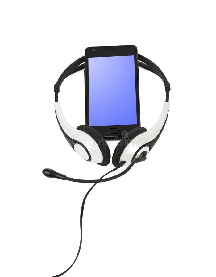 Teléfono móvil y auriculares foto de archivo