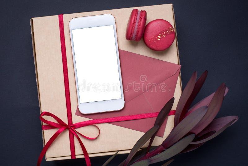 Teléfono móvil y con la flor y el presente en fondo oscuro fotos de archivo