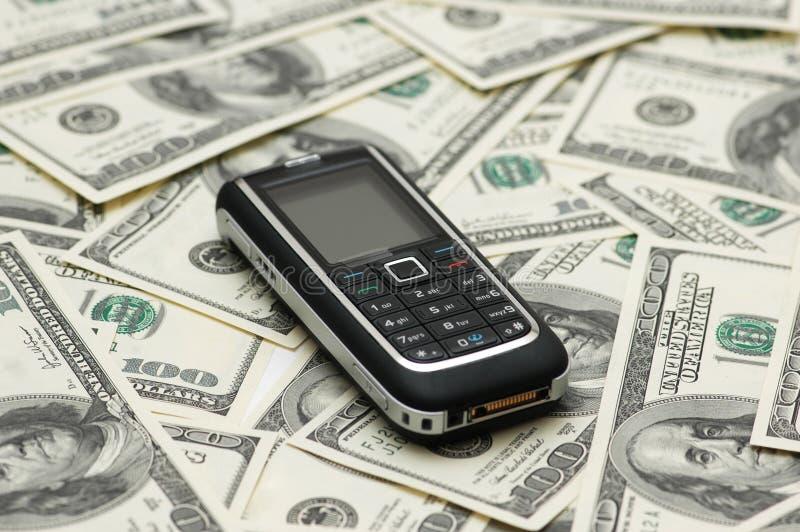 Teléfono móvil y dólares foto de archivo libre de regalías