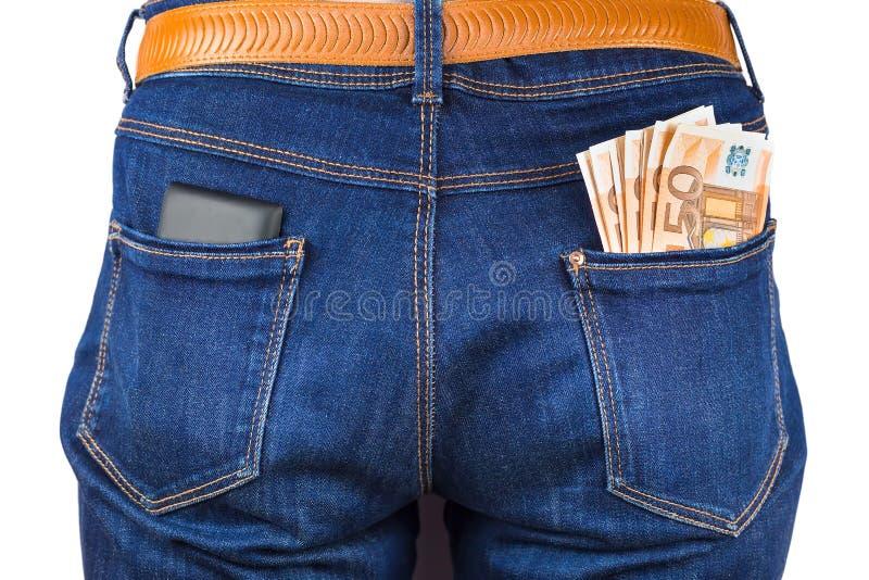 Teléfono móvil y dinero del euro en tejanos imágenes de archivo libres de regalías