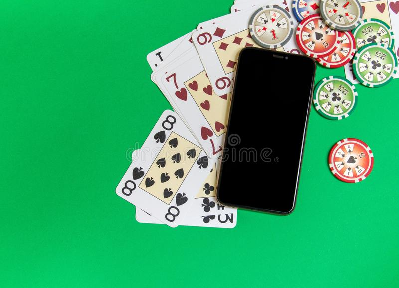 Teléfono móvil y fichas de póker con los naipes en una tabla verde Concepto en l?nea del casino fotos de archivo