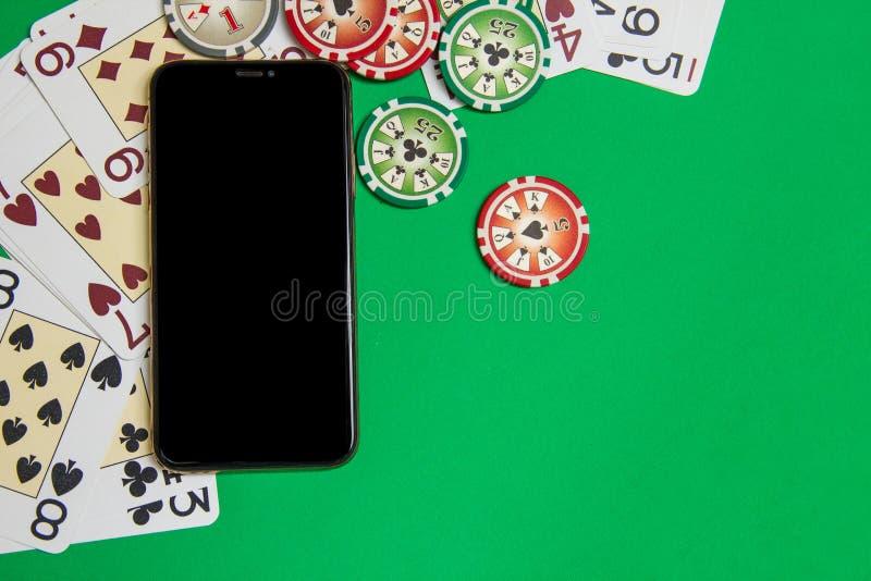 Teléfono móvil y fichas de póker con los naipes en una tabla verde Concepto en l?nea del casino fotos de archivo libres de regalías