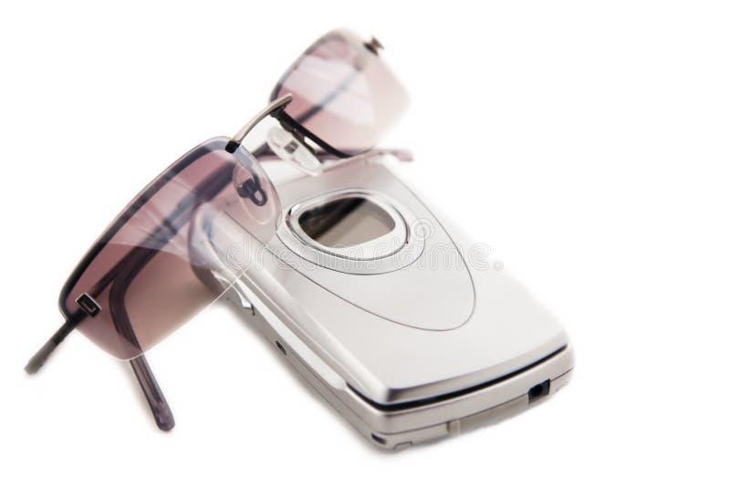 Teléfono móvil y gafas de sol foto de archivo libre de regalías