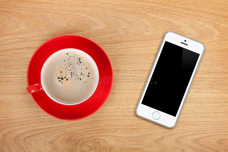 Teléfono móvil y taza de café imagenes de archivo