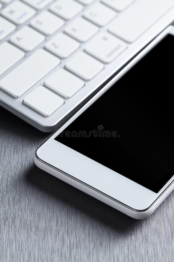Teléfono móvil y teclado de ordenador blancos modernos en un fondo de aluminio gris foto de archivo