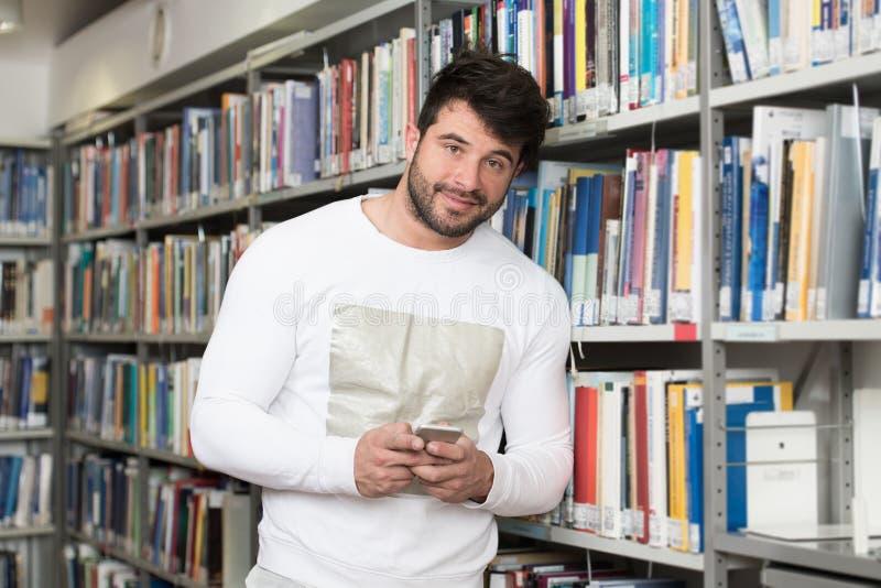 Teléfono masculino hermoso de Typing On Mobile del estudiante universitario fotografía de archivo