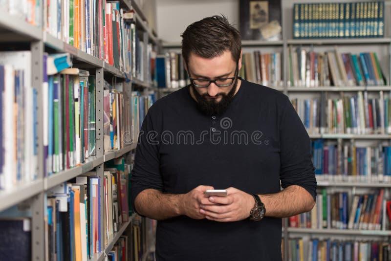 Teléfono masculino hermoso de Typing On Mobile del estudiante universitario imagen de archivo