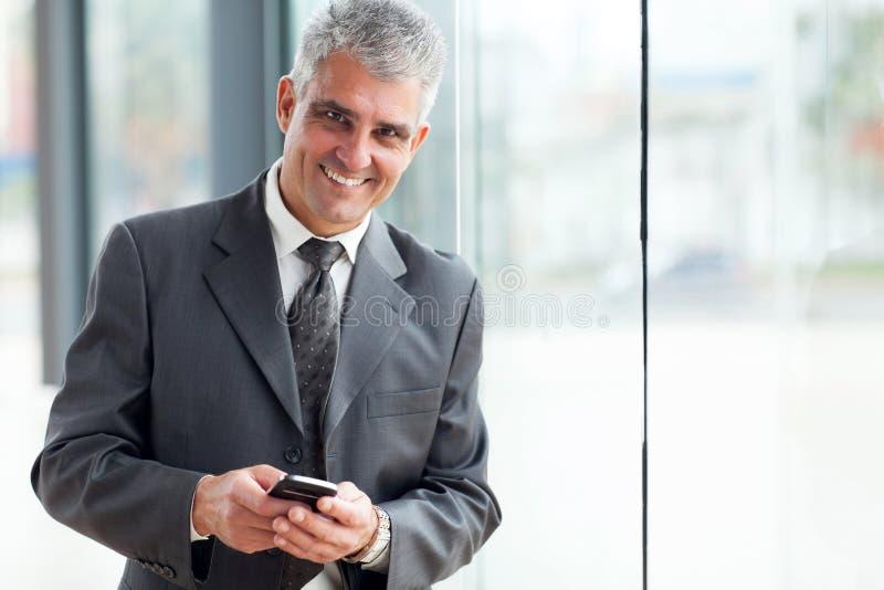 Teléfono mayor del hombre de negocios fotos de archivo