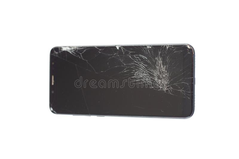Teléfono negro con un sensor y una pantalla quebrados, vidrio agrietado de la pantalla táctil en un isloate blanco del fondo imagenes de archivo