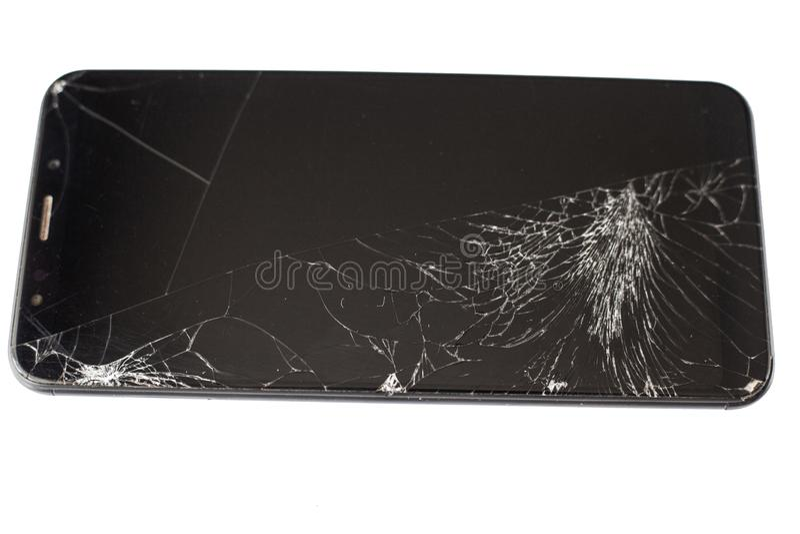 Teléfono negro con un sensor y una pantalla quebrados, vidrio agrietado de la pantalla táctil en un isloate blanco del fondo fotos de archivo