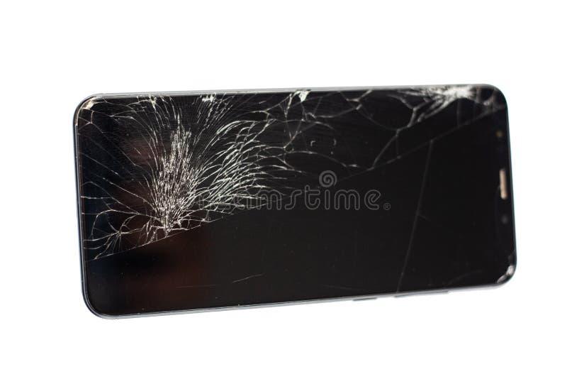 Teléfono negro con un sensor y una pantalla quebrados, vidrio agrietado de la pantalla táctil en un isloate blanco del fondo fotografía de archivo libre de regalías