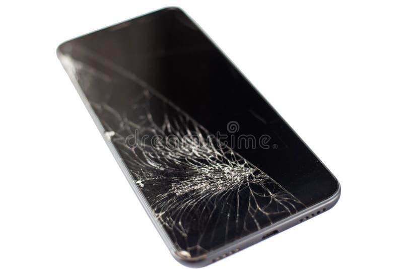 Teléfono negro con un sensor y una pantalla quebrados, vidrio agrietado de la pantalla táctil en un isloate blanco del fondo fotografía de archivo