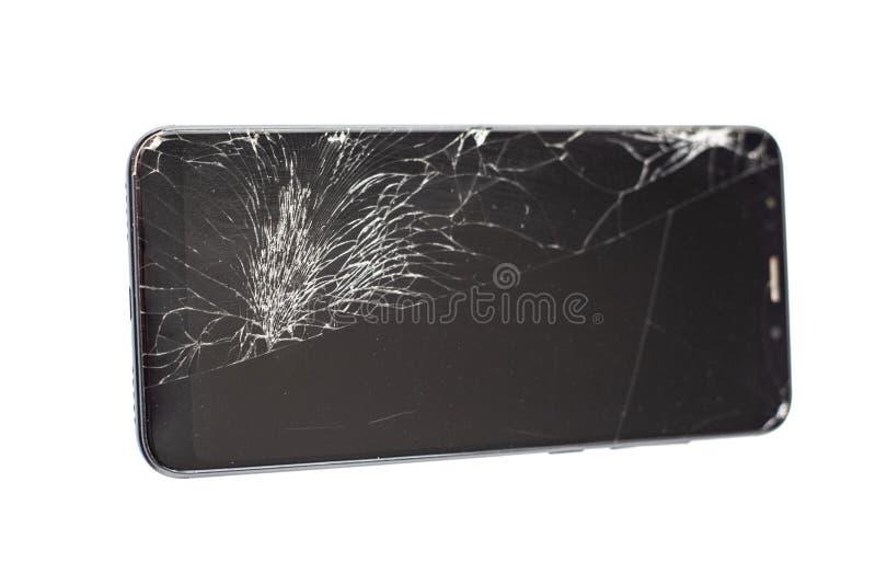 Teléfono negro con un sensor y una pantalla quebrados, vidrio agrietado de la pantalla táctil en un isloate blanco del fondo imágenes de archivo libres de regalías
