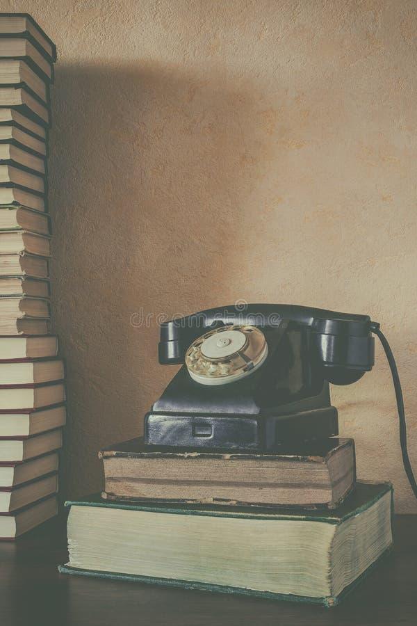 Teléfono negro viejo y una pila de libros fotos de archivo