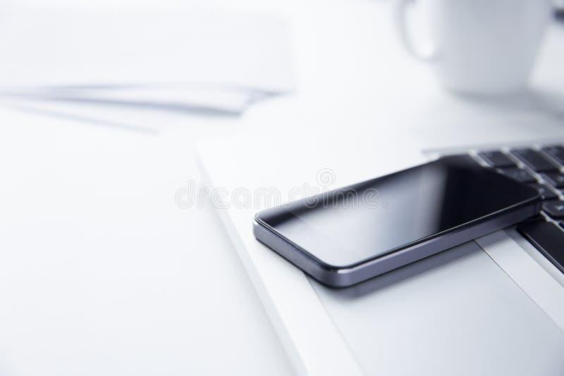 Teléfono que descansa sobre un ordenador portátil imágenes de archivo libres de regalías