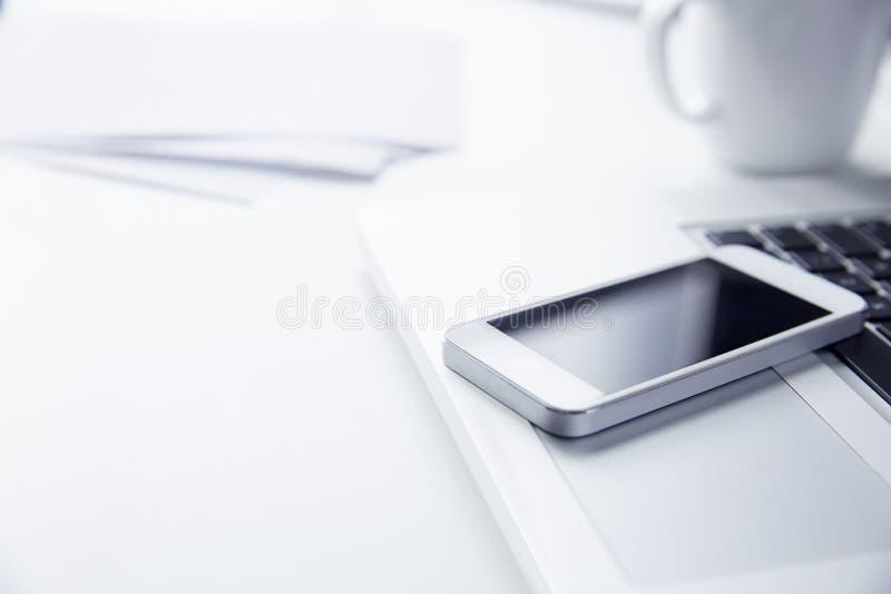 Teléfono que descansa sobre un ordenador portátil imagen de archivo