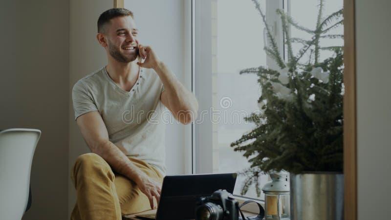 Teléfono que habla atractivo del hombre joven que se sienta en alféizar con el ordenador portátil y la cámara en casa fotos de archivo libres de regalías