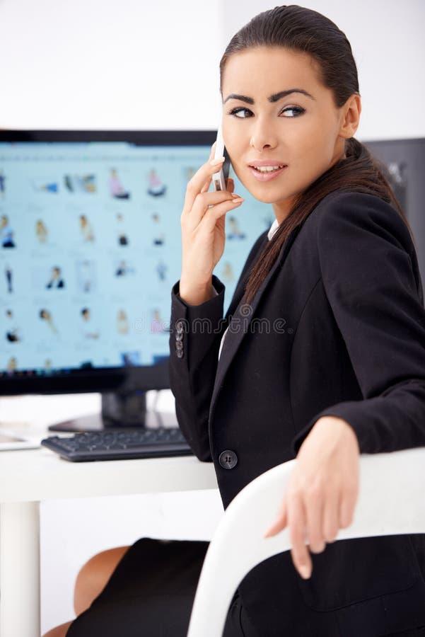 Teléfono que habla de la mujer de negocios mientras que se sienta delante del ordenador fotos de archivo
