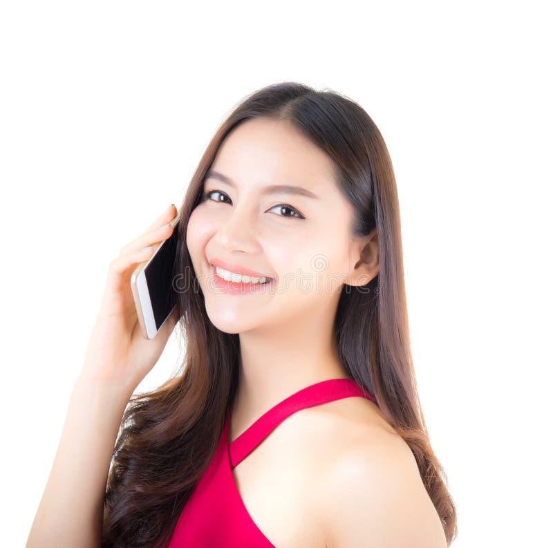 Teléfono que habla de risa del adolescente asiático alegre de la mujer aislado imagen de archivo