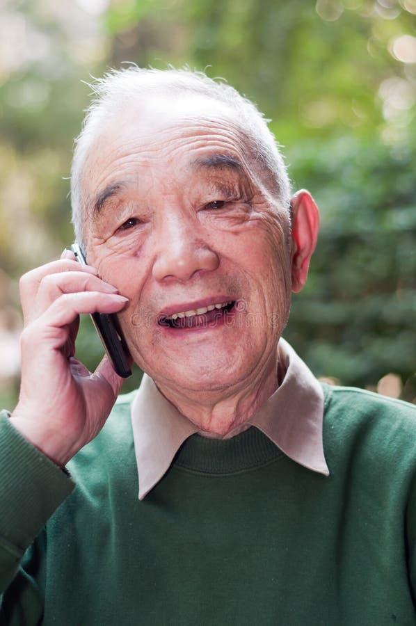 Teléfono que habla de un más viejo hombre imagenes de archivo
