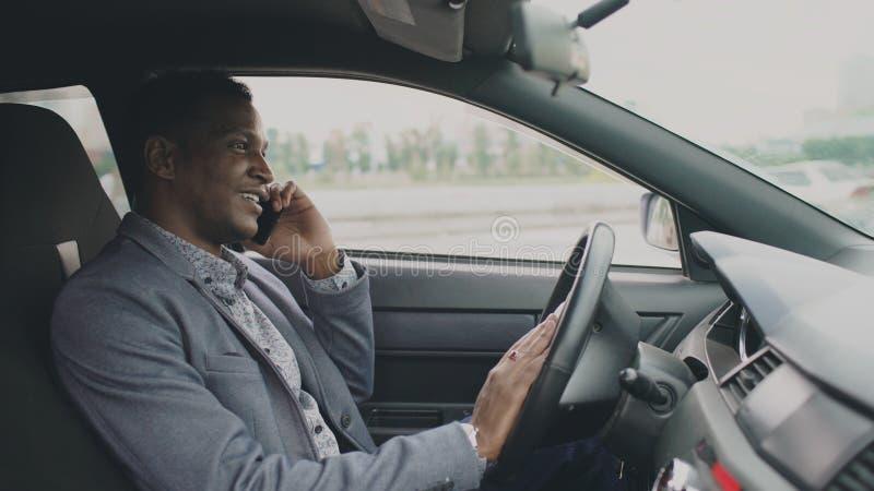 Teléfono que habla del hombre de negocios feliz de la raza mixta mientras que se sienta dentro de su coche al aire libre fotos de archivo