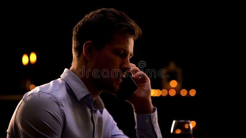 Teléfono que habla del hombre de negocios serio, relajándose en club nocturno después de día del trabajo duro fotos de archivo libres de regalías