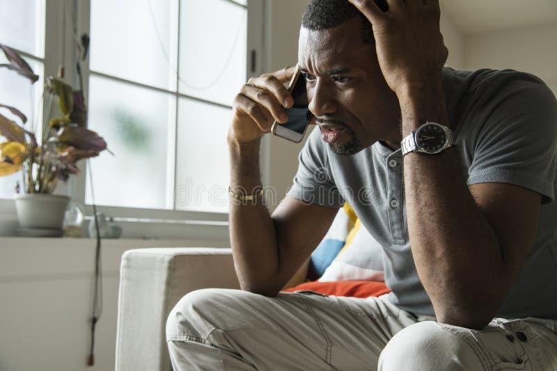 Teléfono que habla del hombre negro con la emoción enojada fotos de archivo