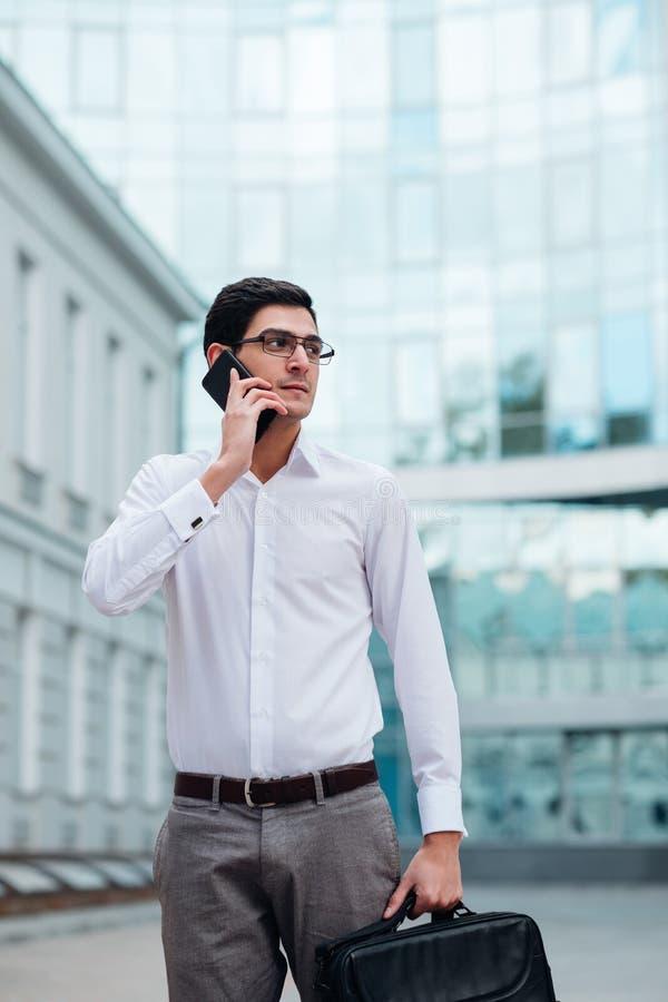 Teléfono que habla del hombre ocupado de la forma de vida del negocio imagenes de archivo
