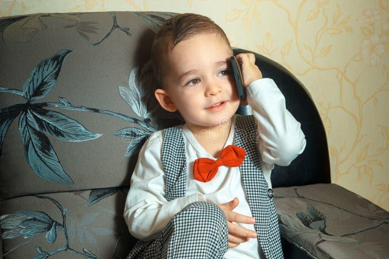Teléfono que habla del niño pequeño fotos de archivo
