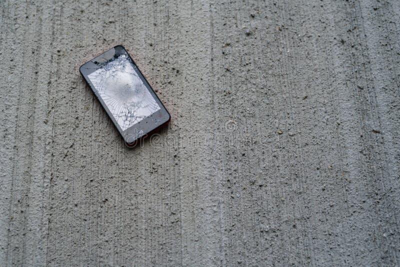Teléfono quebrado en el hormigón fotos de archivo