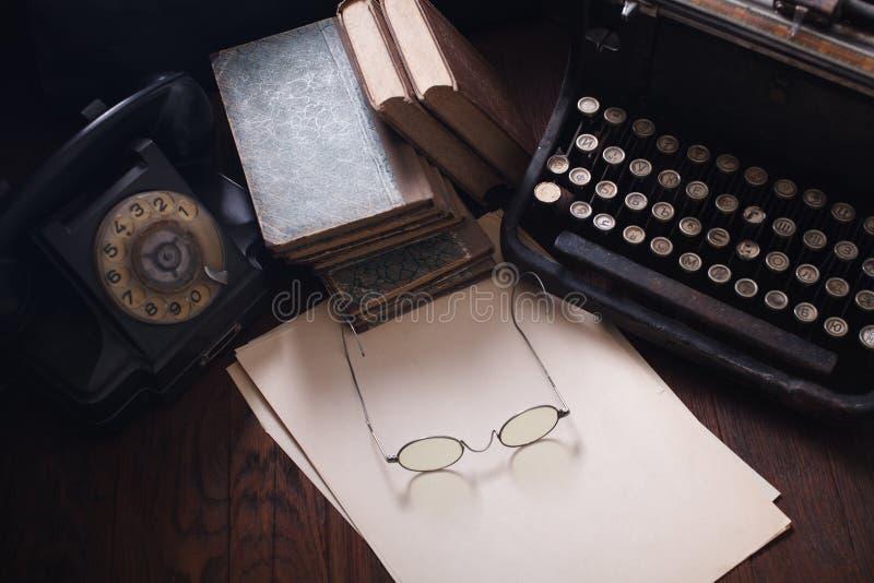 Teléfono retro viejo con la máquina de escribir del vintage y una hoja de papel en blanco en el tablero de madera fotos de archivo