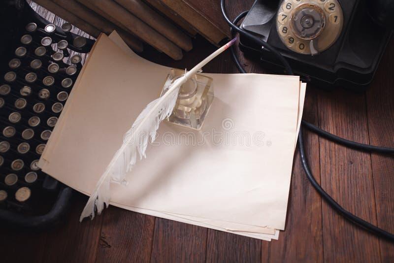 Teléfono retro viejo con la máquina de escribir del vintage y una hoja de papel en blanco en el tablero de madera imagen de archivo libre de regalías