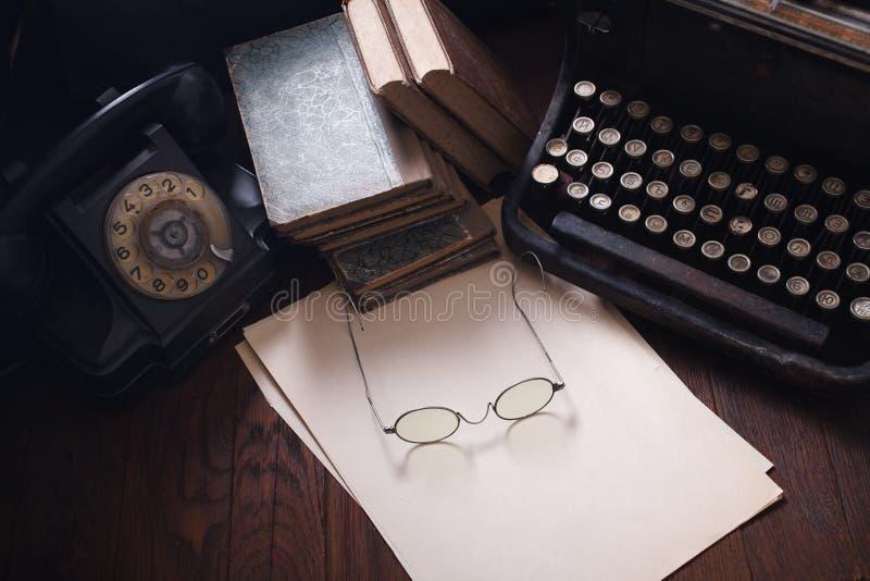 Teléfono retro viejo con la máquina de escribir del vintage y una hoja de papel en blanco en el tablero de madera imagenes de archivo