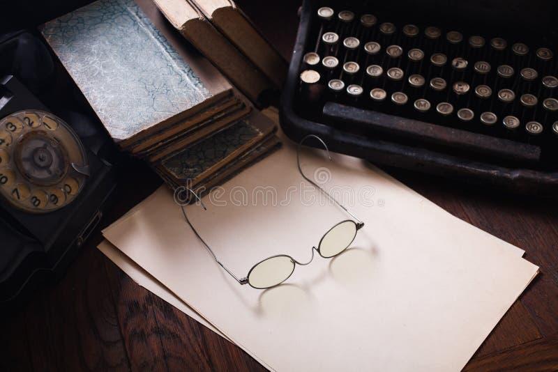 Teléfono retro viejo con la máquina de escribir del vintage y una hoja de papel en blanco en el tablero de madera foto de archivo