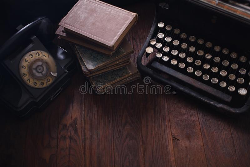 Teléfono retro viejo con la máquina de escribir y los libros del vintage en el tablero de madera imagenes de archivo